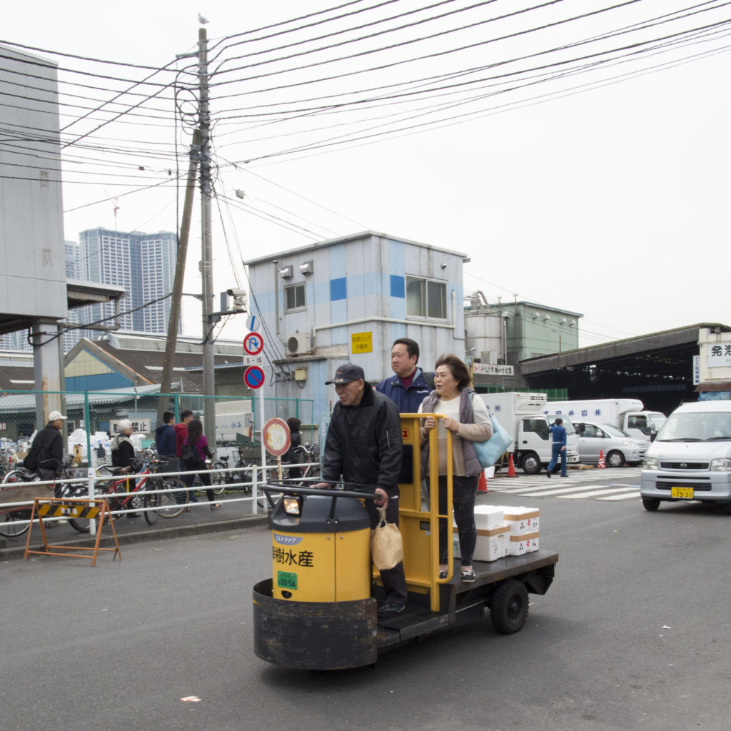 A fish market worker transports two people on a turret cart